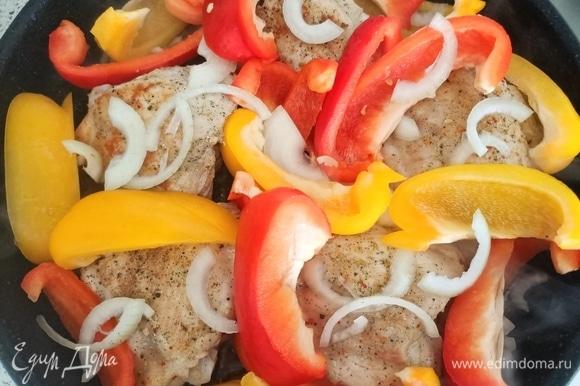 Сверху на мясо выкладываем лук и болгарский перец. Накрываем крышкой и тушим 5 минут.