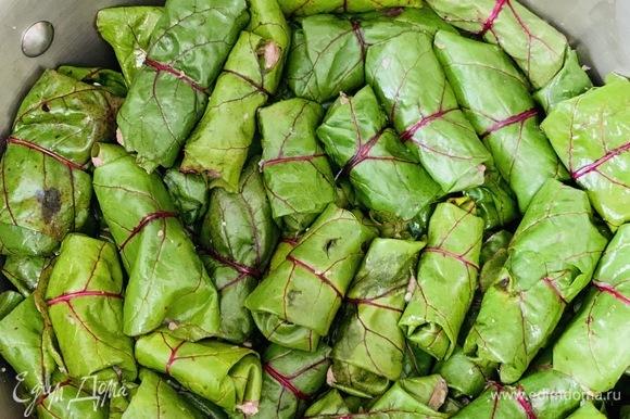 Выкладываем мясо чайной ложной на лист и закручиваем долму, аккуратно выкладывая на дно кастрюли.