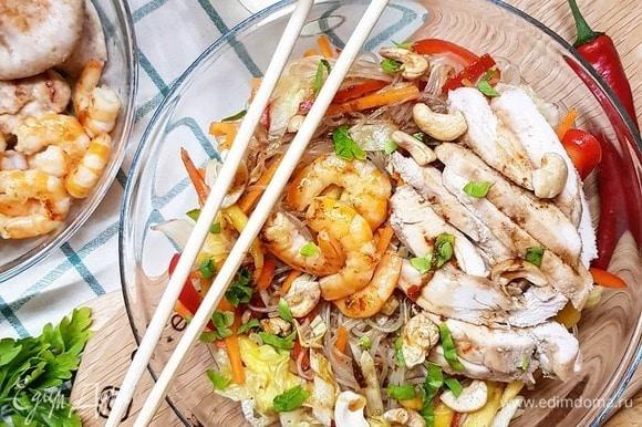 Смешиваем нашу фунчозу с нарезанными овощами и манго, вливаем приготовленный соус. Выкладываем на большое блюдо фунчозу с овощами. Грудку нарезаем слайсами. Поверх лапши выкладываем грудку, креветки, посыпаем все кешью. Выливаем сверху остатки соуса, даем свежей петрушки, если нужно.