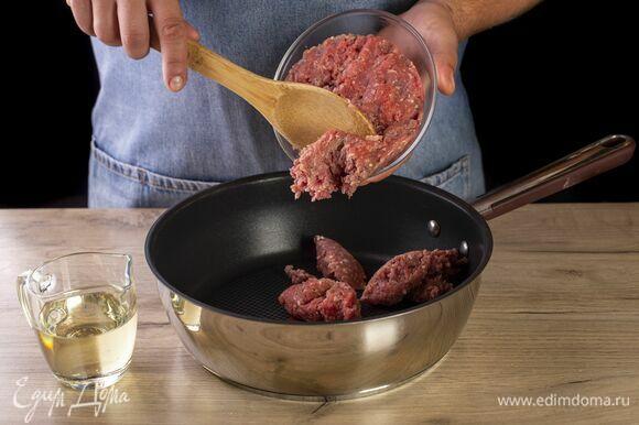 В сковороду налейте растительное масло и выложите фарш. Обжаривайте его, помешивая, около 3 минут. Посолите и поперчите.