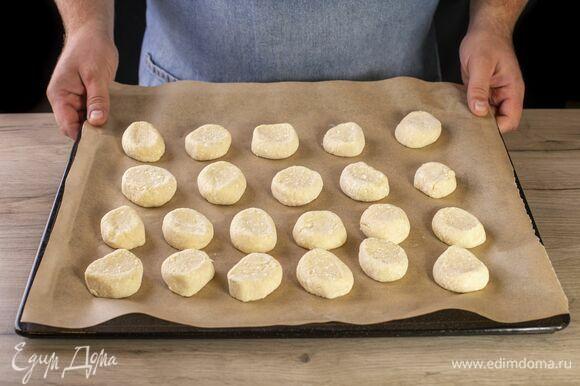 Каждый кусочек теста слегка примните и выложите на застеленный пекарской бумагой противень на небольшом расстоянии друг от друга. Выпекайте в разогретой до 180°C духовке около 15–20 минут до золотистого цвета.
