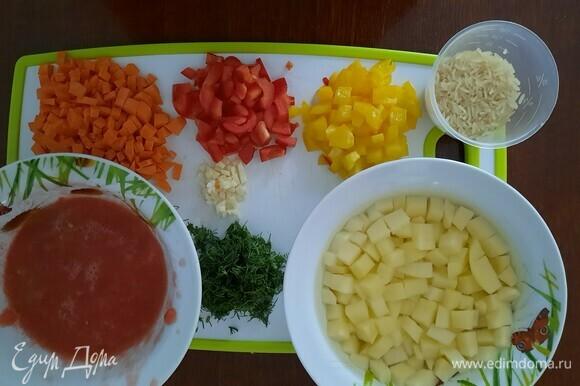Помидор натираем на терке (я взяла 1 большой розовый, можно 2 средних), перец, морковь, картофель нарезаем кубиком. Укроп и чеснок мелко нарезаем. Рис замачиваем в теплой воде, потом хорошо промываем.
