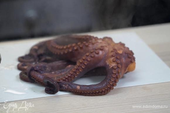 Достать из кастрюли осьминога. Отрезать щупальца.