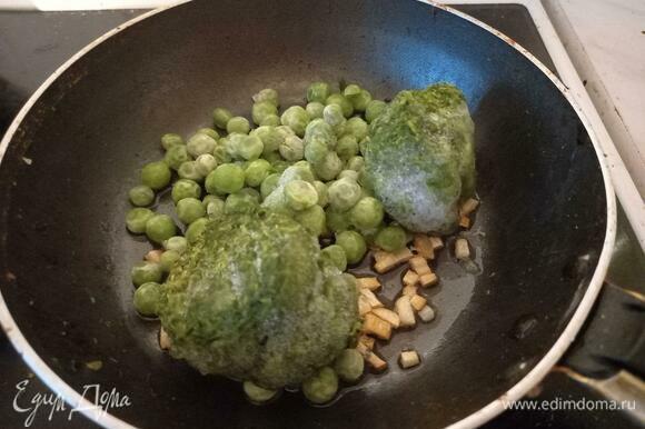 Добавить к чесноку замороженные горошек и шпинат. Закрыть крышкой, оставить на 5 минут. Шпинатные шарики должны расползтись, а горошек стать мягким.