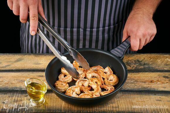 Пожарьте креветки на сковороде в оливковом масле около 2 минут.