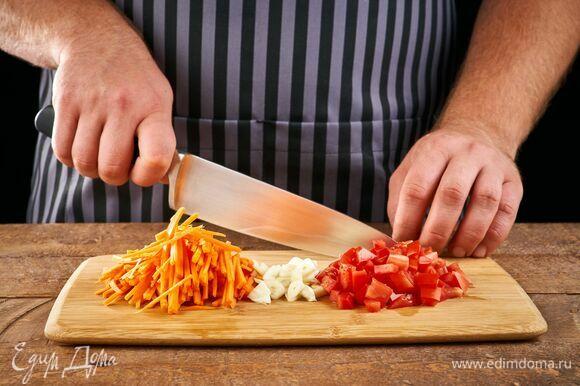 Морковь нарежьте соломкой. Чеснок мелко порубите. Помидор нарежьте мелкими кубиками.