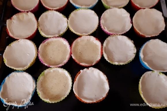 Разделите тесто на несколько частей. Каждую часть раскатайте достаточно тонко (2–3 мм). Вырежьте из теста кругляшки и поместите их в формочки для маффинов так, чтобы они закрывали стенки. Налейте внутрь начинку. Есть два варианта пирожных: можно их оставить как есть, а можно прилепить «крышечки» из теста сверху. Так как у меня начинки получилось меньше, чем теста, большинство пирожных я закрыла.