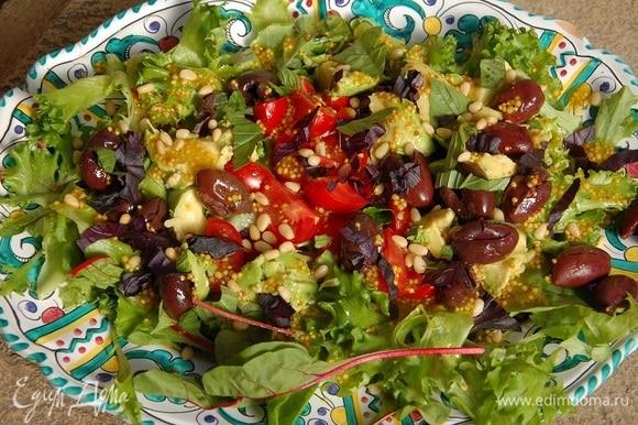 Салатные листья, нарезанные помидоры, мякоть авокадо и оливки, выложить на блюдо, полить все заправкой, посыпать измельченным базиликом и кедровыми орехами.