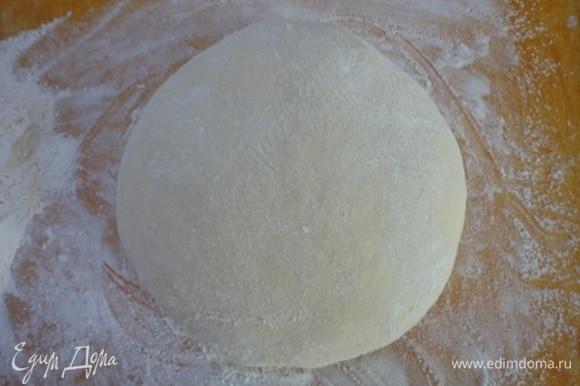 Накрыть миску с тестом и оставить примерно на 2 часа, пока тесто не вырастет вдвое. Когда тесто подошло, обмять его и выложить на посыпанную мукой поверхность. Разделить на 15–16 частей (примерно по 65–70 г теста на каждую булочку).