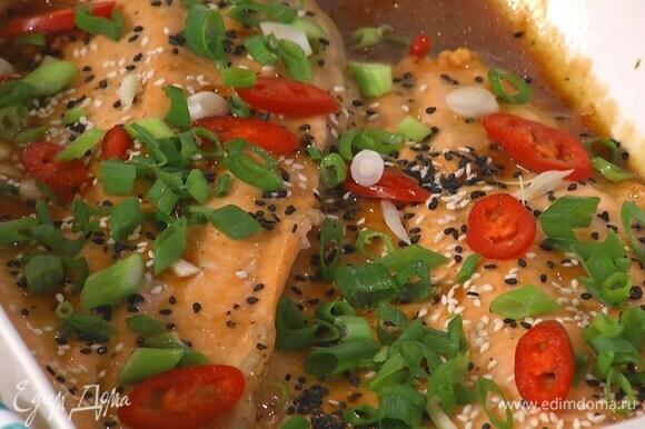 Готовую рыбу посыпать белым и черным кунжутом, чесноком, перцем чили и зеленым луком.