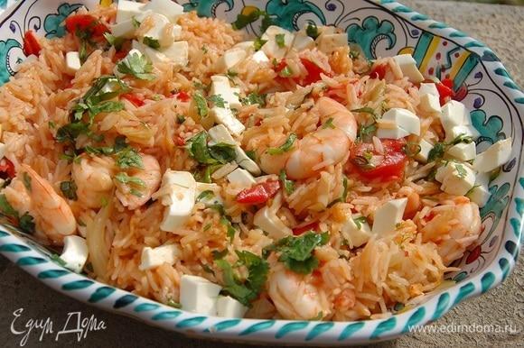 Готовый рис с овощами и креветками выложить на блюдо, посыпать измельченной зеленью, сбрызнуть оливковым маслом Extra Virgin, сверху разложить фету.