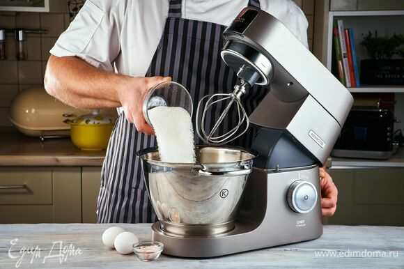 В чаше кухонной машины взбейте венчиком до однородного состояния яйца, сахар и соль.
