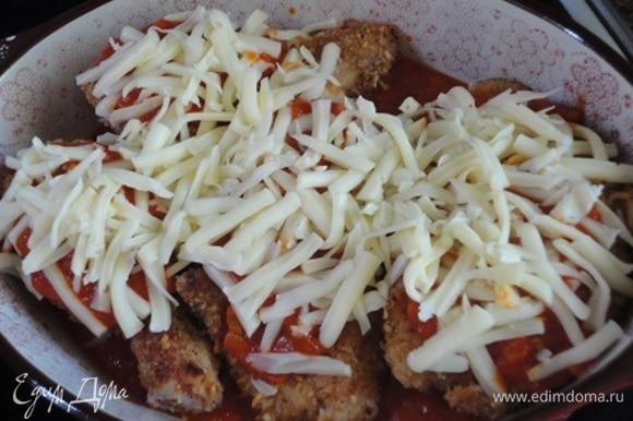 На каждый кусочек курицы выложить небольшое количество томатного соуса. Посыпать тертой на крупной терке полутвердой моцареллой. Не надо заливать толстым слоем соуса всю курицу.