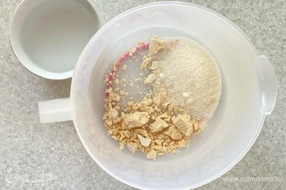Дрожжи раскрошить в мерный стакан, добавить половину сахара и воду. Перемешать до растворения, оставить на 5–10 минут, до начала брожения.