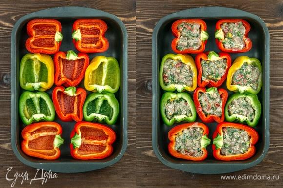 В форму для запекания выложите половинки перцев, затем заполните их ароматной куриной начинкой.
