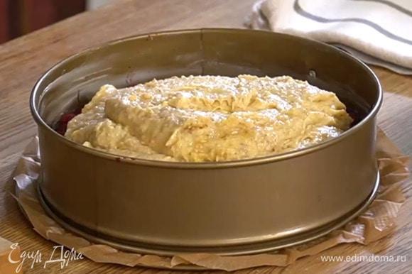 Выстелить дно разъемной формы бумагой для выпечки, смазать дно и стенки оставшимся сливочным маслом и равномерно выложить джем, затем в один слой плотно уложить вишню, накрыть тестом и разровнять его.