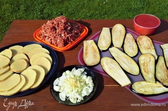 У баклажанов отрезать плодоножку. Нарезать вдоль длинными полосками толщиной 0,5 см. Лук почистить, некрупно нарезать. Чеснок почистить и измельчить. Картофель помыть, нарезать кружками. Мякоть мяса прокрутила через мясорубку. С помидоров сняла кожицу, взбила в блендере. В томатное пюре добавила кетчуп, можно томатную пасту.