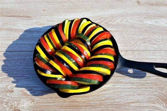 На половину соуса выложить «змейкой» колечки баклажанов, кабачков и помидоров, чередуя овощи по цвету. Оставшийся соус нанести сверху, стараясь заполнить им пространство между колечками.