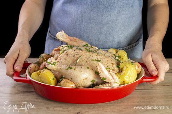 Переложите курицу на противень. Добавьте картошку, моченые яблоки и розмарин. Запекайте в духовке 1 час при 180°C. Каждые 20 минут поливайте маслом.