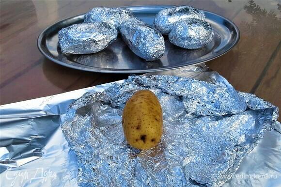 Картошку тщательно помыть губкой. Фольгу для запекания смазать растительным маслом и посолить. Завернуть картошку в два слоя фольги.