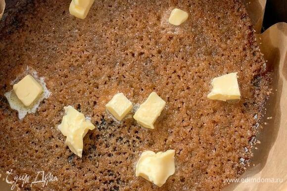 На горячий сахар выложите кусочки сливочного масла (25 грамм).