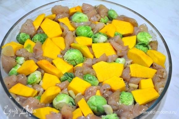 Замаринованное филе выкладываем ровным слоем на смазанную растительным маслом форму для запекания. Тыкву и капусту равномерно распределяем по курице, немного вдавливая их между кусочками филе.