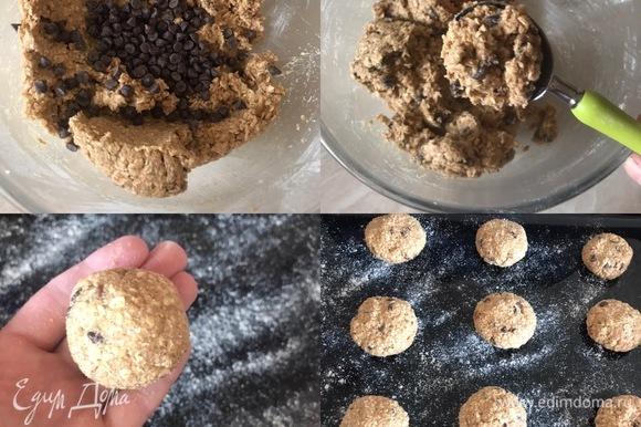 В конце добавить шоколадные капли и еще раз хорошо перемешать. Противень слегка посыпать мукой. Из теста сформировать шарики, слегка приплюснуть рукой и разложить.