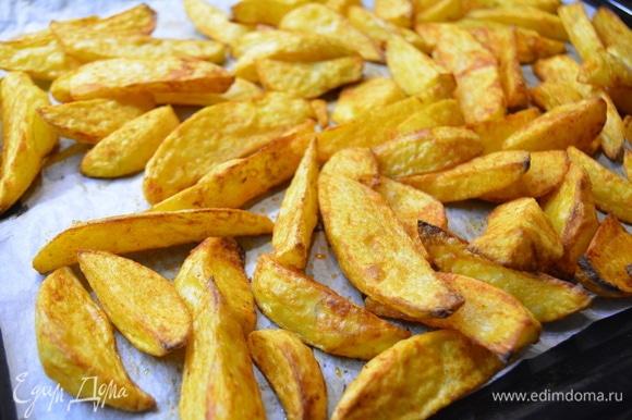 Достать готовый картофель и сразу подавать, пока он хрустящий снаружи, а внутри — нежная мякоть.