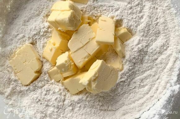 В миске смешайте пшеничную муку (просейте), сахарную пудру, разрыхлитель и щепотку соли. Холодное сливочное масло нарежьте кубиком и добавьте к муке. Перетрите тесто в крошку.