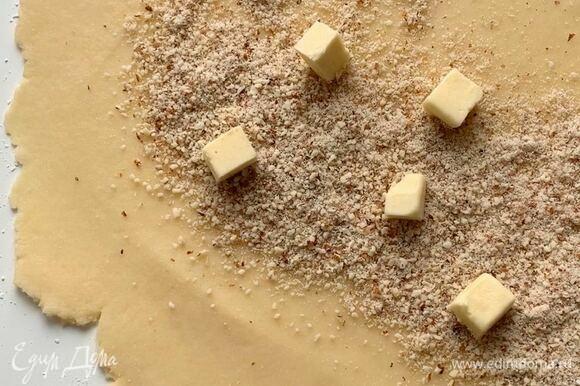 Достаньте тесто из холодильника, раскатайте толщиной 5–6 мм. По короткому краю посыпьте миндальной крошкой (бороздку толщиной 5 см), сверху выложите кубики сливочного масла.