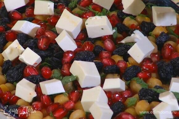 Готовый нут переложить на блюдо, полить оставшимся оливковым маслом, апельсиновым соком, посыпать цедрой, мятой, посолить, поперчить, сверху выложить изюм, чили, зерна граната, фету и запеченные морковь с луком.
