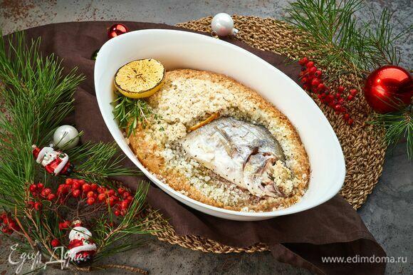 Запекайте рыбу в предварительно разогретой до 200°С духовке 20 минут. При помощи щипцов извлеките горячую рыбу и выложите на блюдо. Украсьте и подавайте к праздничному столу!