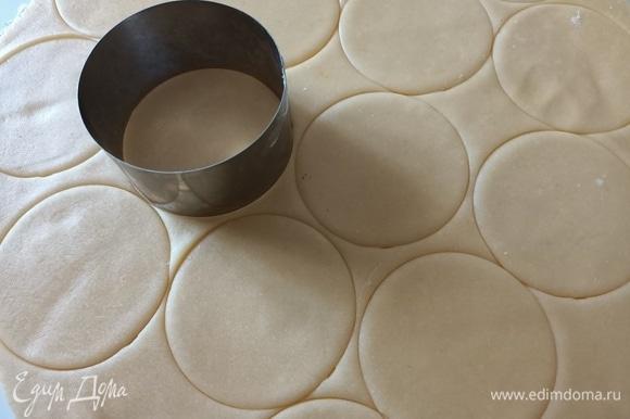 Рабочую поверхность посыпать мукой. Раскатать песочное тесто. Круглой формой диаметром 8 см вырезать заготовки для корзинок.