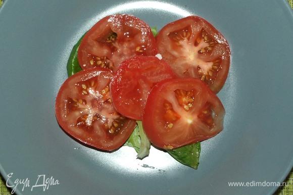 В тарелку кладем немного листьев салата, сверху помидор и немного заправки.