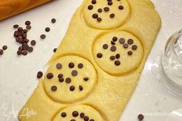 По истечении времени тесто раскатать в пласт толщиной 1 см и вырезать круги. Сверху посыпать шоколадными каплями или шоколадом. Немного вдавить в тесто. Выпекать на пергаменте 15–20 минут (до румяности) при 185°C.