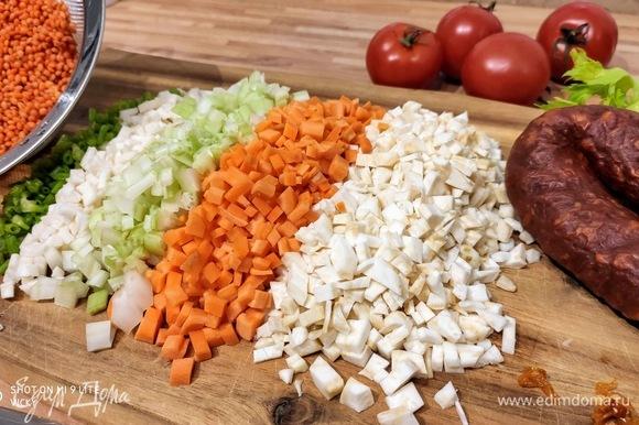 Очистите лук, морковь, корень петрушки, оба вида сельдерея, кусочек перца чили и нарежьте мелкими кубиками размером с чечевицу. Использовать ли перец чили — решайте сами. Чаще всего колбаски чоризо уже достаточно острые, поэтому остроту регулируйте по своему вкусу. В большой кастрюле разогрейте сливочное и оливковое масло и обжарьте лук на медленном огне. Я нашинковала стебли петрушки и добавила их к овощам. Также можно использовать пастернак и/или любой другой из корешковых овощей.