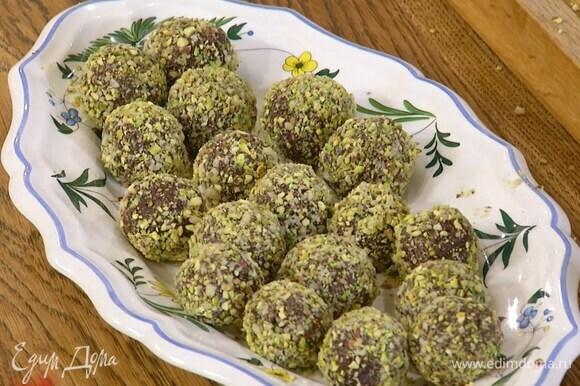 Сформировать небольшие шарики и обвалять их в измельченных фисташках и кедровых орехах.