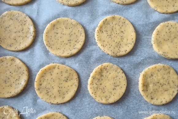 Раскатать тесто, с помощью круглой формы вырезать заготовки для будущего печенья. Противень застелить пергаментной бумагой выложить тесто и поставить в предварительно разогретую до 180°C духовку примерно на 10 минут, пока печенье не станет слегка золотистого цвета.