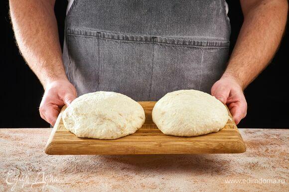 По окончании программы достаньте тесто, оно будет липким. Смочите руки водой и разделите тесто на две части.