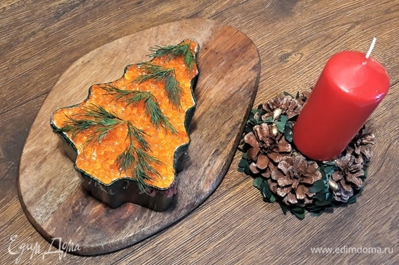Теперь нашу «Новогоднюю елку» надо поставить в холод хотя бы на 2 часа, чтобы она пропиталась ароматами продуктов. Поставим под колпак или накроем фольгой, чтобы икра не заветрилась. Потом украсим веточками укропа — сделаем ей зеленый наряд! Следующий этап самый сложный — надо потянуть за пленку и достать салат из формы.