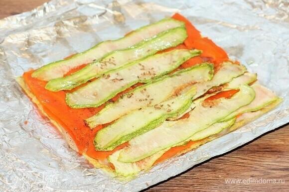 Кладем пластины кабачка на морковь, посыпаем приправой для овощей, перцем и солью.