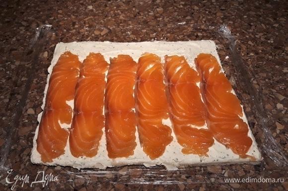 На пищевую пленку уложите хлеб слегка внахлест по три кусочка в два ряда. Скалкой примните, чтобы не было швов. Смажьте хлебный пласт творожно-сливочным сыром. Сверху выложите полоски рыбы.