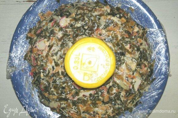 Края плоского блюда застелить пищевой пленкой. В центр блюда поставить стакан. Салат выложить вокруг стакана в форме кольца, слегка утрамбовывая.