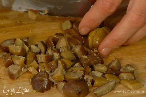 Каштаны нарезать мелкими кубиками, выложить к луку с чесноком и слегка обжарить, затем добавить грибы вместе с вином и все потушить.