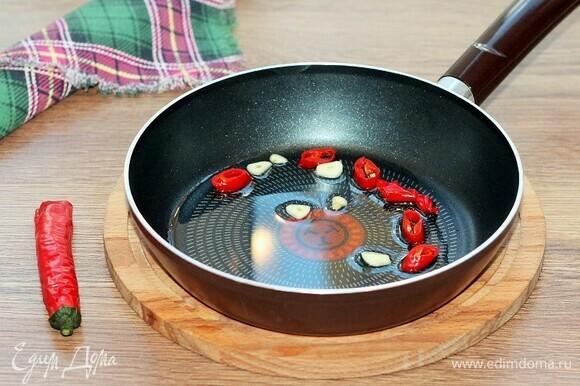 На разогретом подсолнечном масле обжариваем острый перец и чеснок. Затем овощи убираем, масло оставляем.