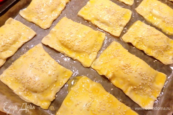 Слойки выкладываем на противень, застеленный пергаментной бумагой. Взбиваем яйцо, смазываем слойки и посыпаем кунжутом. Отправляем в духовку при 190°C на 30–40 минут, ориентируйтесь на свою духовку.
