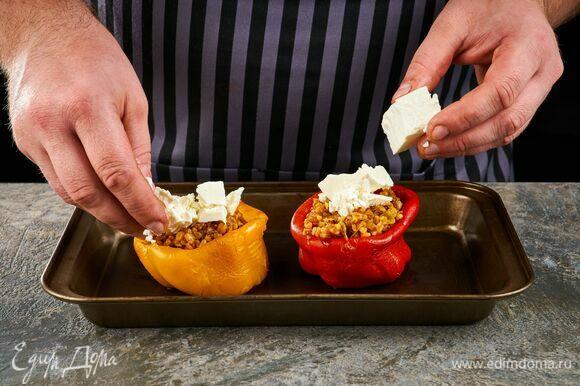 Начините получившейся смесью запеченные перцы. Добавьте мелко покрошенную фету. Отправьте обратно в духовку на 5 минут.