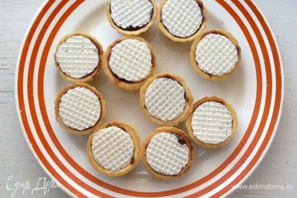 Вафельными кружками закрыть донышки пирожных. Поставить заготовки в морозилку на 5–8 минут.