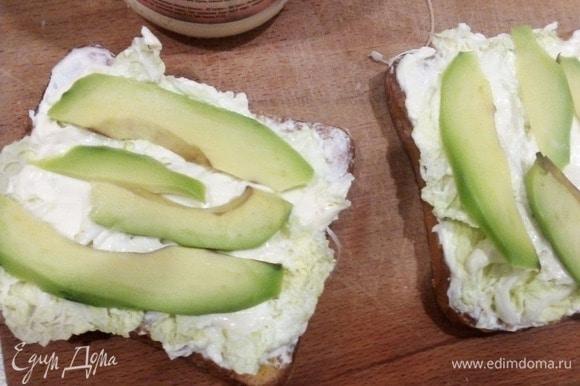 Собираем сэндвичи. Густо мажем сыром кусочки хлеба без яйца в центре, «приклеиваем» на него листья салата или пекинской капусты. Сверху еще сыр выкладываем и нарезанное слайсами авокадо. Закрываем все хлебом с яичком, посыпаем зеленью. В общем-то, все. Приятного!
