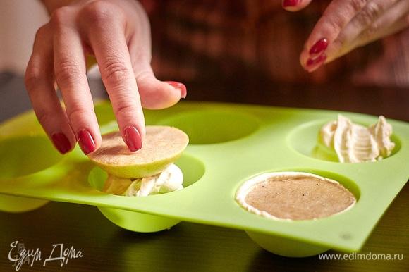 Часть крема выложите в формочки, туда воткните банановую начинку.